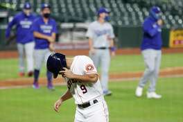 Houston Astros infielder Jack Mayfield walks back to the dugout as the Los Angeles Dodgers celebrate after the they beat the Astros 4-2 in the thirteenth inning of an MLB baseball game at Minute Maid Park, Wednesday, July 29, 2020, in Houston.