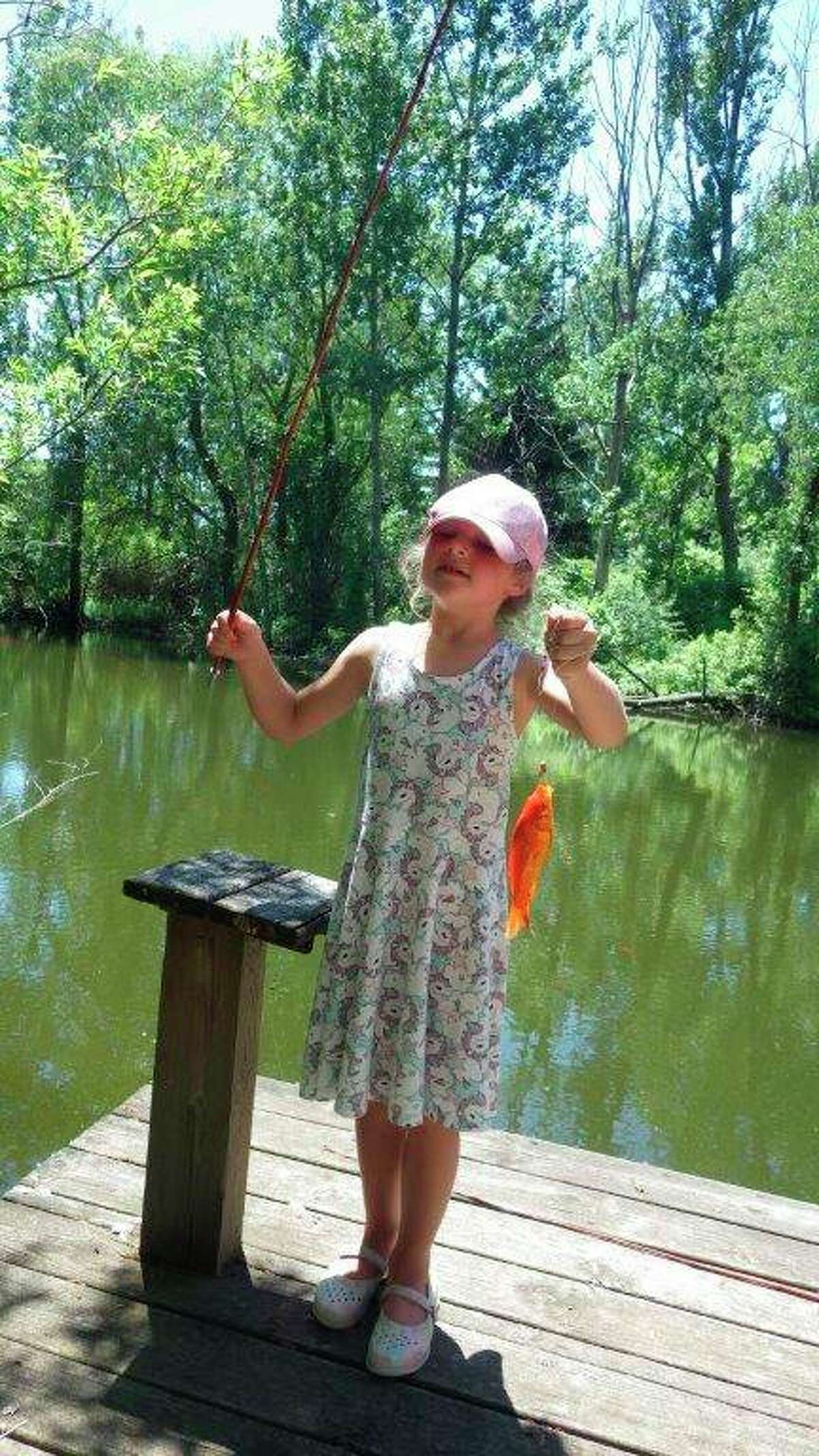 RosaMae Lounsbury, 7 years old in this photo, thoroughly enjoys fishing with a cane pole inher grandparents' farm pond, where she hooked this trophy goldfish. (Tom Lounsbury/Hearst Michigan)