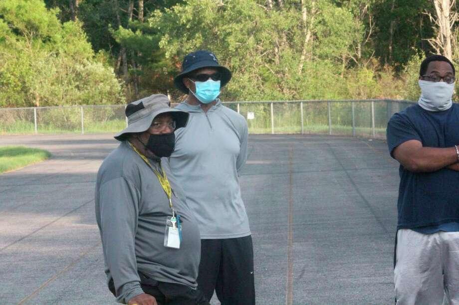Baldwin coach Robert Watkins (left) and his assistants talk to the team last week. (Star photo/John Raffel)