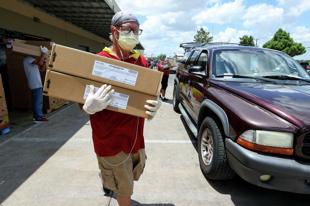 Wayne Poisson carries boxes of food items to a waiting family while volunteering at the San Antonio Food Bank in July.