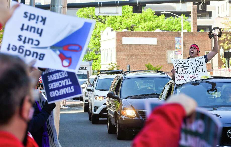 """Davenport teacher James Darling II, at right, shouts """"No Cuts"""" as passes by with students, teachers, parents, and other community members as they hold a rolling rally caravan around the Stamford Government Center on May 21, 2020, in a unified show of support to urge city officials to fund Stamford schools and not impose more than $15 million in cuts to education, which they say would be devastating to students, especially during the coronavirus pandemic. Photo: Matthew Brown / Hearst Connecticut Media / Stamford Advocate"""