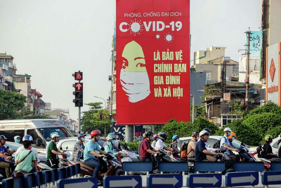 Motorcyclists pass a billboard with public information about coronavirus in Hanoi, on May 29, 2020. Photo: Bloomberg Photo By Maika Elan / Bloomberg