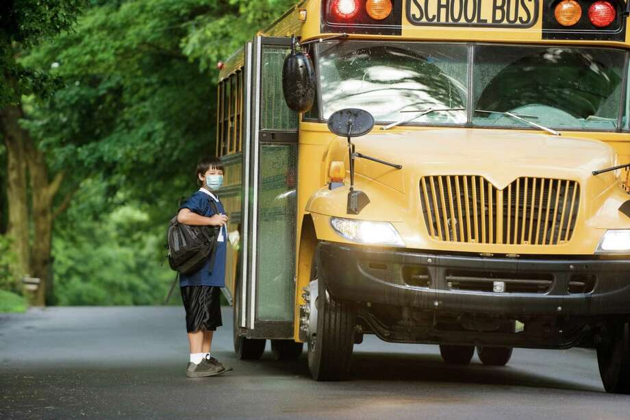School bus picking up elementary student wearing surgical mask boarding at bus stop. Photo: Nycshooter / Getty Images / E+
