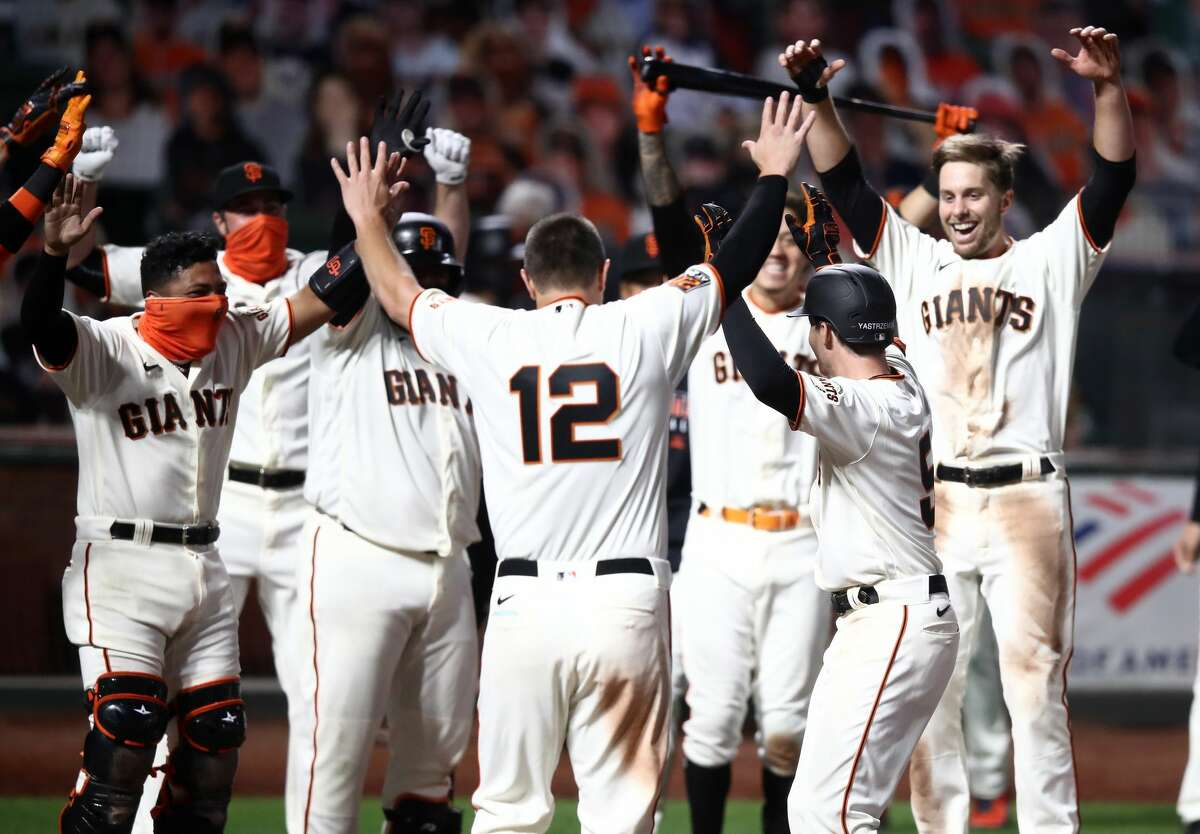 Mike Yastrzemski #5 of the San Francisco Giants celebrates with teammates after he hit a walk-off home run in the ninth inning against the San Diego Padres at Oracle Park on July 29, 2020 in San Francisco, California. (Photo by Ezra Shaw/Getty Images)