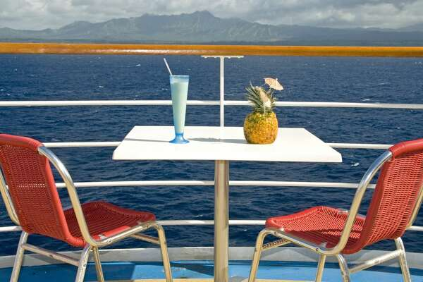 View of cocktails and the islands off the back upper deck of a cruise ship.