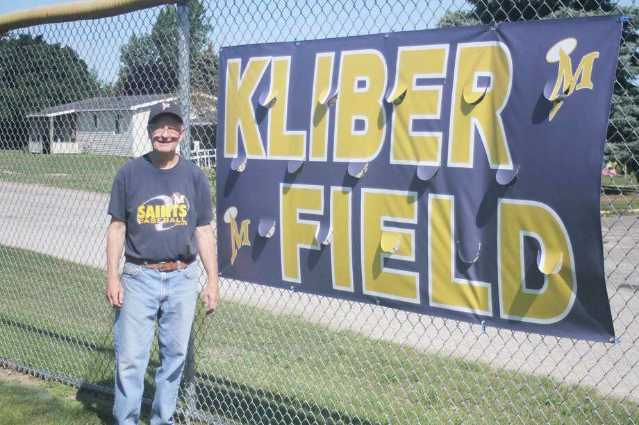 Members of the Manistee Saints family present the new banner, honoring Phil Kliber at a recent ceremony to dedicate the field in his name. (Dylan Savela/News Advocate)