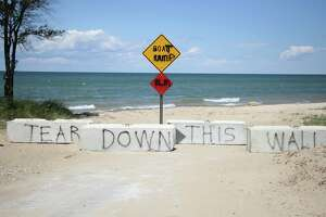 """Concrete barricades recently placed in front of Oak Beach boat launch were defaced when someone spray painted """"Tear down this wall."""" (Mark Birdsall/Huron Daily Tribune)"""