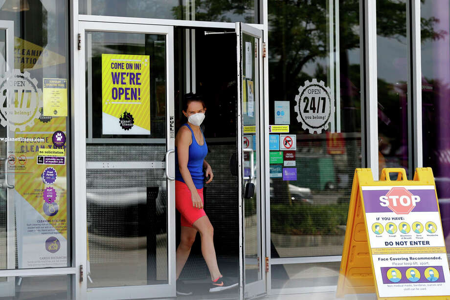 A person wears a mask while leaving a Planet Fitness gym location. Planet Fitness will require masks at all locations beginning Saturday. Photo: Nam Y. Huh | AP / Copyright 2020 The Associated Press. All rights reserved.