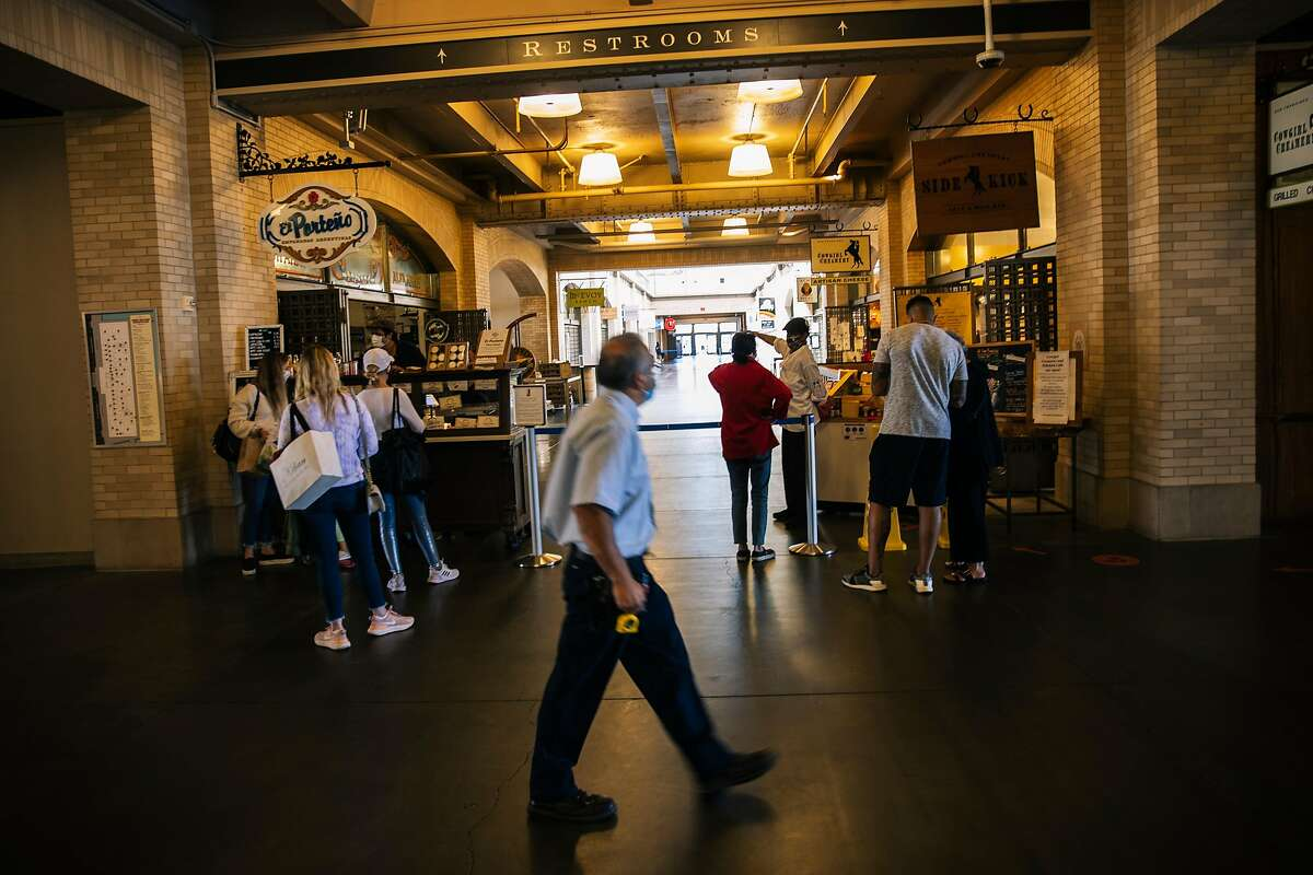 People wait in lines for El Porteno and Cowgirl Creamery along a passage way in the Ferry Building after all interior shops were forced to shut down due to the ongoing COVID-19 pandemic in San Francisco, Calif. on Thursday, July 23, 2020.