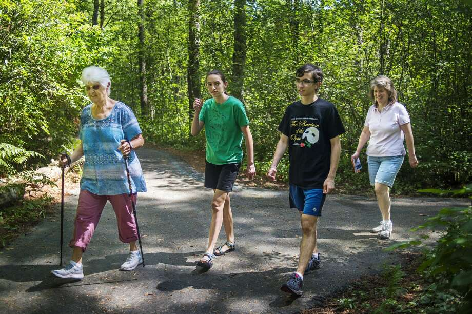 From left, Priscilla Deskins, Cara Bucci, 13, Ben Bucci, 15, and Alysia Bucci, all of Midland, walk down one of the trails surrounding MidMichigan Medical Center-Midland as they participate in a Walk Midland event Thursday, July 30, 2020. Walks are schedule each day of the week, except for Saturday, at varying locations, through Wednesday, Aug. 5. More information can be found at www.cityofmidlandmi.gov. (Katy Kildee/kkildee@mdn.net) Photo: (Katy Kildee/kkildee@mdn.net)
