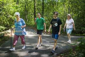 From left, Priscilla Deskins, Cara Bucci, 13, Ben Bucci, 15, and Alysia Bucci, all of Midland, walk down one of the trails surrounding MidMichigan Medical Center-Midland as they participate in a Walk Midland event Thursday, July 30, 2020. Walks are schedule each day of the week, except for Saturday, at varying locations, through Wednesday, Aug. 5. More information can be found at www.cityofmidlandmi.gov. (Katy Kildee/kkildee@mdn.net)