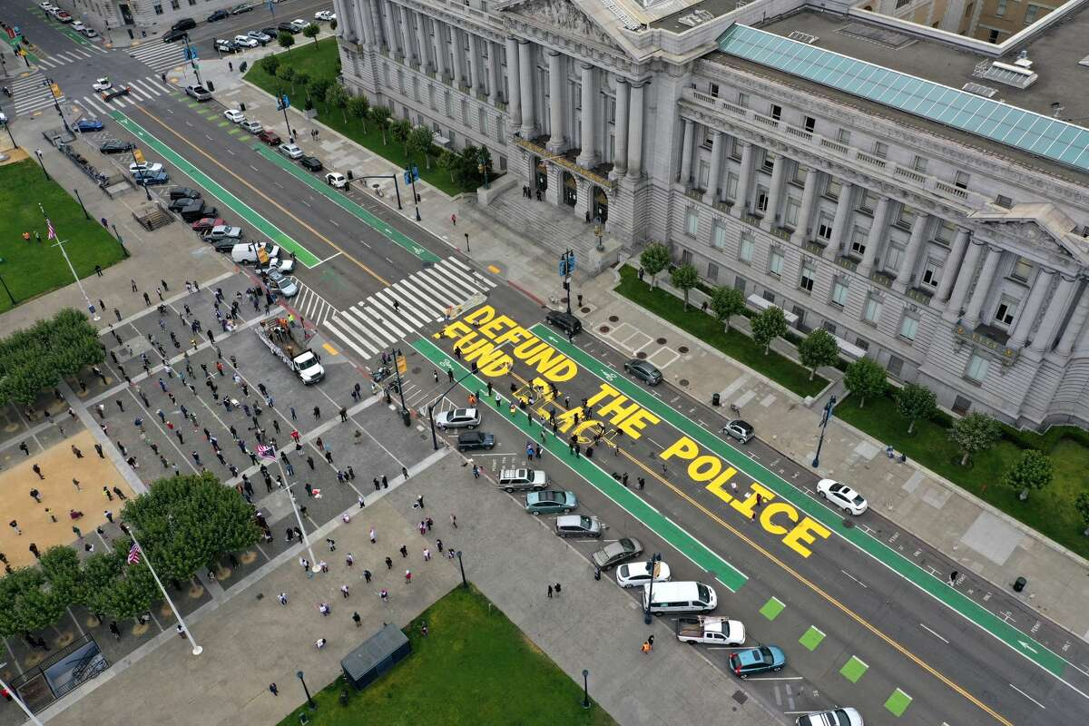 Protesters paint a mural that says 'defund the police' during a Strike For Black Lives demonstration outside of San Francisco City Hall on July 20, 2020. The demonstration was part of the nationwide Strike for Black Lives effort which is calling for higher wages, better jobs, and Unions to help workers build economic power.