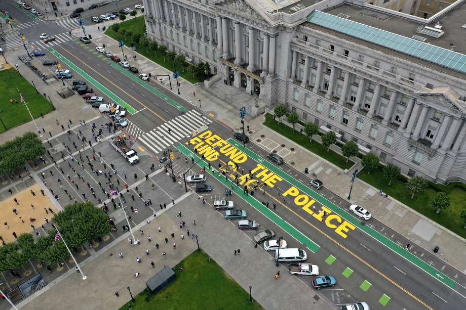 Protesters paint a mural that says 'defund the police' during a Strike For Black Lives demonstration outside of San Francisco City Hall on July 20, 2020. The demonstration was part of the nationwide Strike for Black Lives effort which is calling for higher wages, better jobs, and Unions to help workers build economic power. Photo: Justin Sullivan/Getty Images / 2020 Getty Images