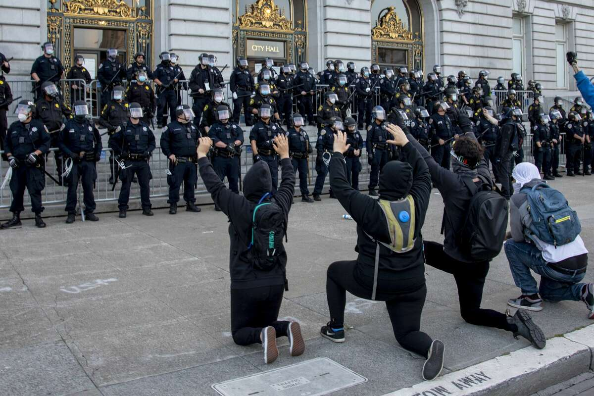 Protesters kneel in front of heavily-guarded San Francisco City Hall, Sunday, May 31, 2020, the third day of Bay Area unrest over the George Floyd killing in Minneapolis. The encounter was tense but remained peaceful.
