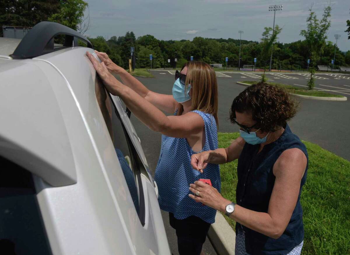 Susan DeCarlo, left, of Bethel, with Bethel High School, and Rosemary Dunn, of Bethel, with King Street Intermediate School, tape a sign to a car as teachers in Danbury joined colleagues, parents, students and community members across the state who held simultaneous School Safety First Car Caravans demanding the state provide for safety, equity and funding when schools reopen. Thursday, July 30, 2020, at Danbury High School, in Danbury, Conn.