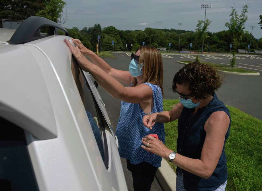 Susan DeCarlo, left, of Bethel, with Bethel High School, and Rosemary Dunn, of Bethel, with King Street Intermediate School, tape a sign to a car as teachers in Danbury joined colleagues, parents, students and community members across the state who held simultaneous School Safety First Car Caravans demanding the state provide for safety, equity and funding when schools reopen. Thursday, July 30, 2020, at Danbury High School, in Danbury, Conn. Photo: H John Voorhees III / Hearst Connecticut Media / The News-Times