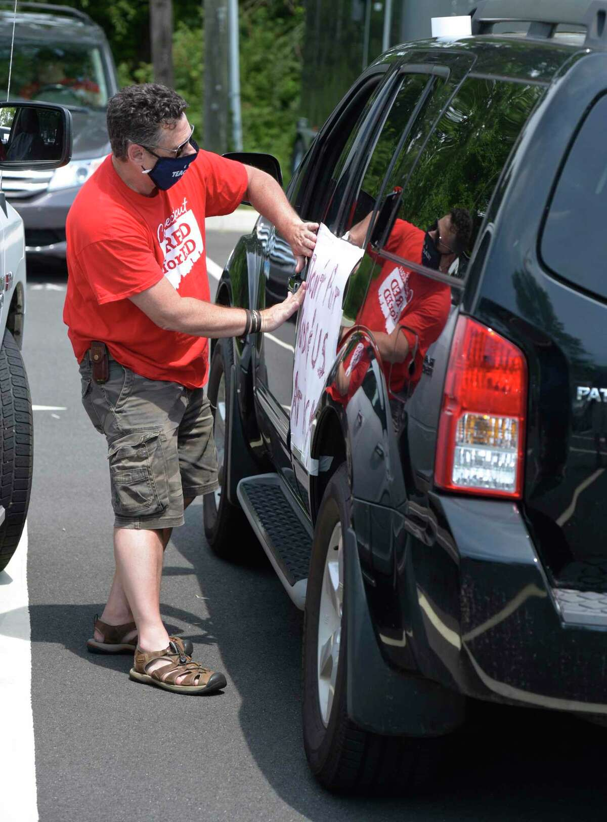 Thomas Ross, of Danbury, with Danbury High School, tapes a sign to his car as teachers in Danbury joined colleagues, parents, students and community members across the state who held simultaneous School Safety First Car Caravans demanding the state provide for safety, equity and funding when schools reopen.