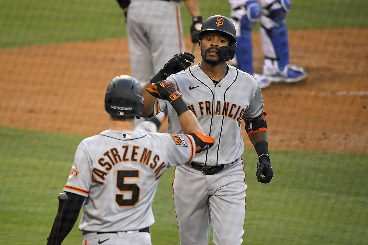 San Francisco Giants' Jaylin Davis, right, is congratulated by Mike Yastrzemski after hitting a solo home run during the third inning of a baseball game against the Los Angeles Dodgers Friday, July 24, 2020, in Los Angeles. (AP Photo/Mark J. Terrill)