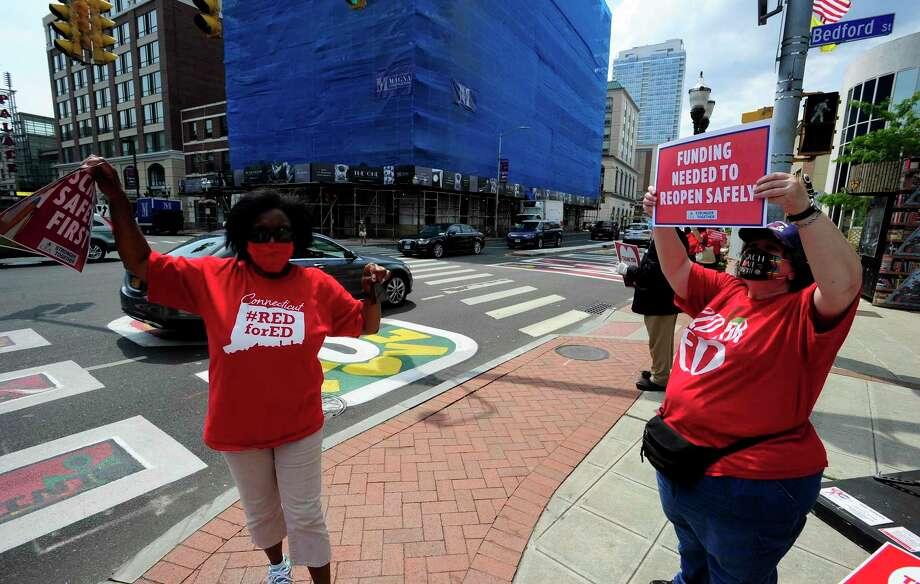"""Stamford teachers Bonita Maddox and Bettina Vaccaro stand outside of the Ferguson Library on the corner of Broad and Bedford Streets soliciting passing motorists to beep their horns as they wait for a car caravan of fellow teachers to pass by there location on July 30, 2020 in Stamford, Connecticut. The teachers union, Stamford Education Association, participated in the CEA's """"School Safety FIRST Car Caravan Rally"""" calling attention to safety concerns in the schools as Connecticut contemplates a return to classes post Covid-19 in the fall. Photo: Matthew Brown / Hearst Connecticut Media / Stamford Advocate"""