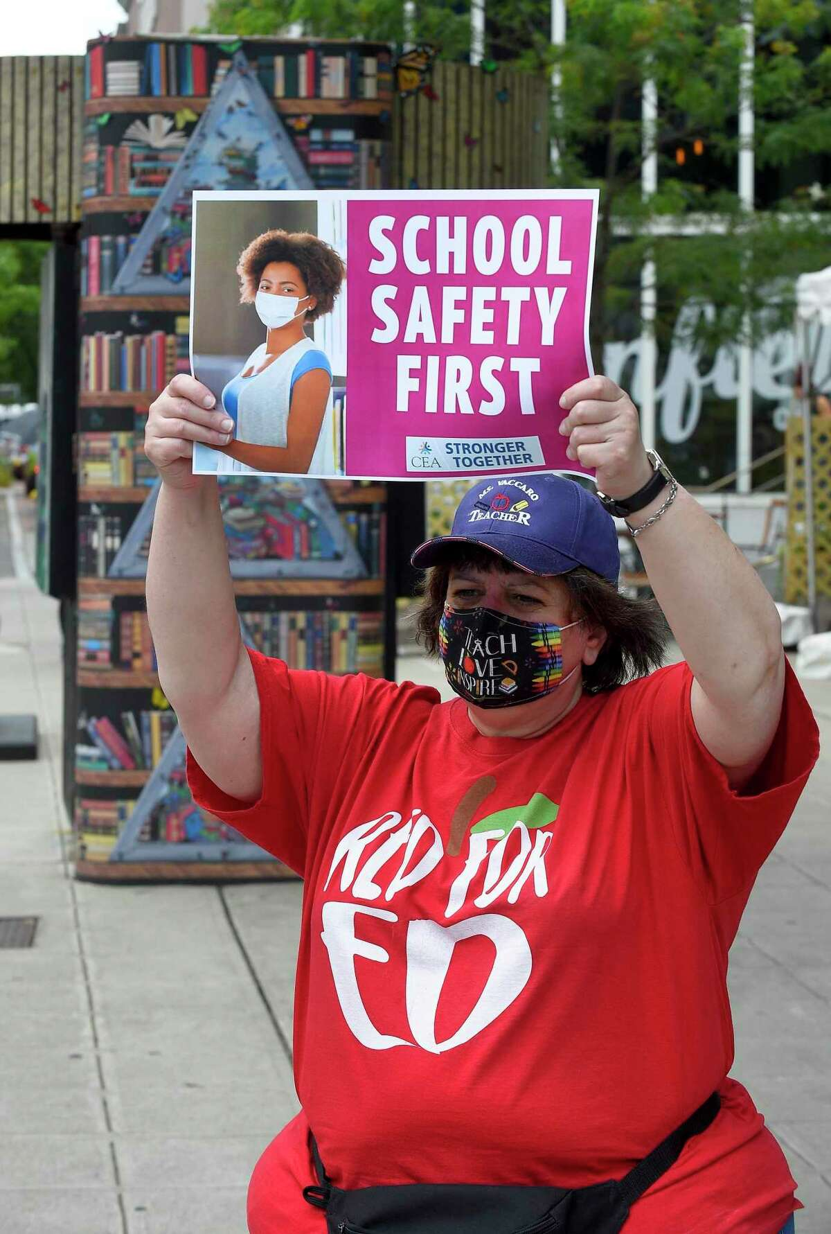 Stamford teachers Bettina Vaccaro stands outside of the Ferguson Library on the corner of Broad and Bedford Streets soliciting passing motorists to beep their horns as a car caravan of fellow teachers pass by on July 30, 2020 in Stamford, Connecticut. The teachers union, Stamford Education Association, participated in the CEA's