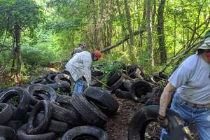 More than 20 volunteers removed 188 old tires from the wooded area beside Little Pond Trail.