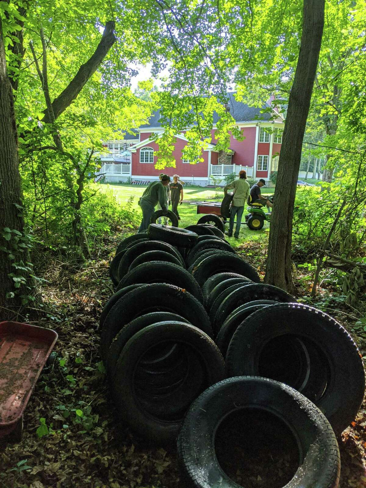 More than 20 volunteers dragged 188 old tires from the wooded area beside Little Pond Trail.