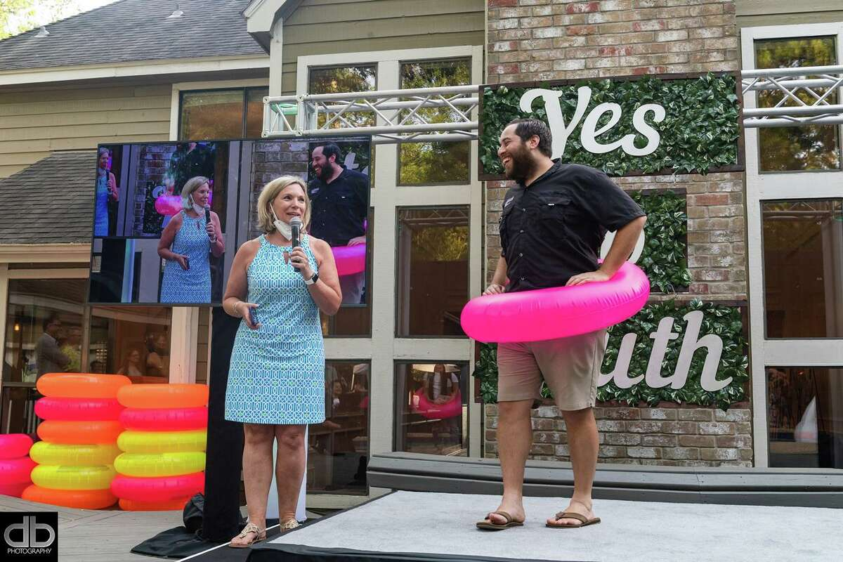 Ann Wolford of The Wolford Group and Zach Richmond share a light-hearted moment as they explain the COVID-19 safety measures and precautions to the limited-attendance guests, such as the use of brightly-colored innertubes for fun social distancing.