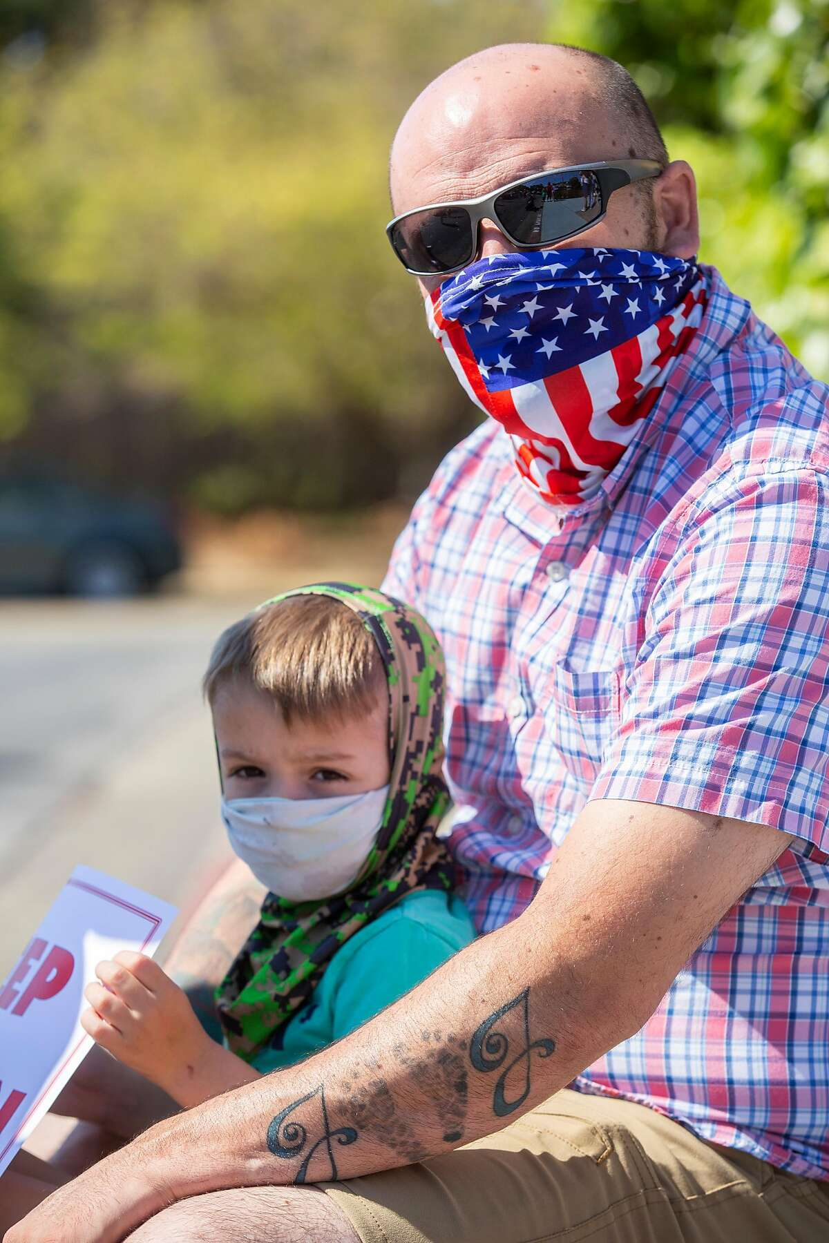 Joe Pelleriti and his son Joe Pelleriti Jr., 3, at a rally outside the Marin County Office of Education on Thursday, July 16, 2020, in San Rafael, Calif. Teachers and their supporters across California are protesting school district plans for in-person learning, amid the coronavirus pandemic. Pelleriti�s spouse Tricia Pelleriti was laid off from her third grade teaching job.