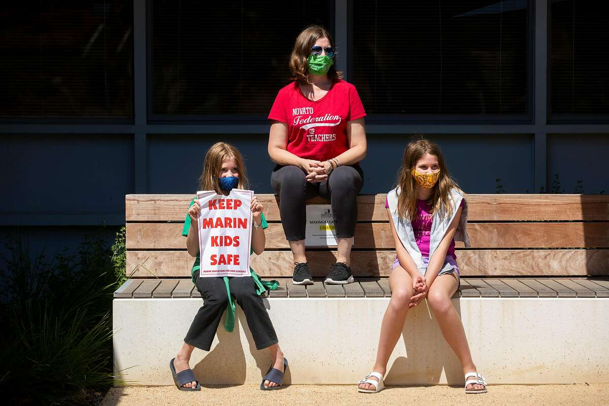 Mariah Fisher (top) with her children (from left) Abby, 10, and Ellie, 12, outside the Marin County Office of Education on Thursday, July 16, 2020, in San Rafael, Calif. Teachers and their supporters across California are protesting school district plans for in-person learning, amid the coronavirus pandemic. Mariah is the president of the Novato Federation of Teachers.