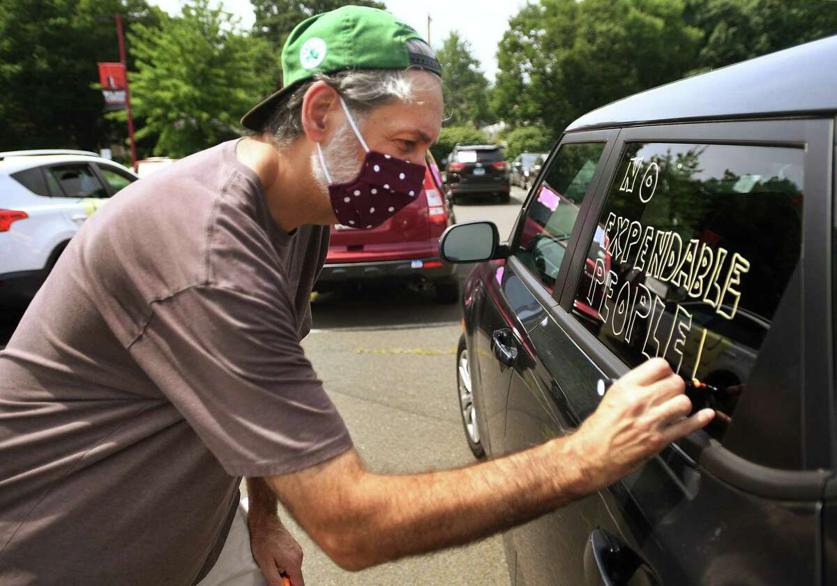 """Scott Meikle, a theater arts teacher at Cooperative Arts & Humanities High School, decorates his car for the New Haven Federation of Teachers caravan for a """"safe and equitable"""" school reopening at Wilbur Cross High School in New Haven, Conn., on Thursday, July 30, 2020."""