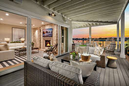 The upper level features a wraparound covered deck overlooking the water.