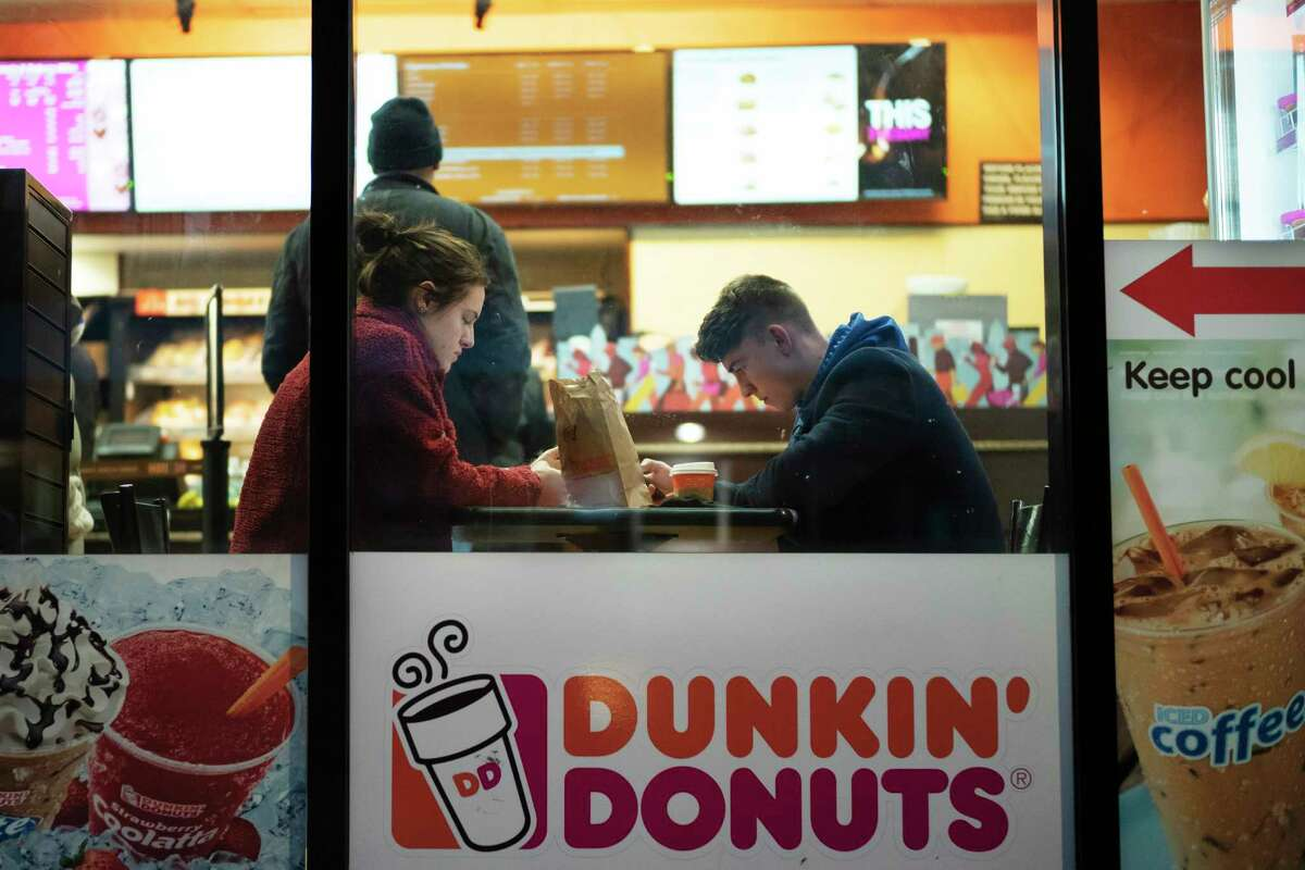 FILE- In this Jan. 30, 2019, file photo customers sit inside a Dunkin' Donuts in New York. Dunkina€™ Brands Inc. on Thursday, July 30, 2020, expects to close up to 800 underperforming U.S. stores this year as it tries to shore up its portfolio in the wake of the coronavirus pandemic. Around 450 of those stores are located within Speedway gas stations. Dunkin' says closing the restaurants would allow their franchisees to reinvest in newer stores in higher-traffic areas.(AP Photo/Mark Lennihan, File)