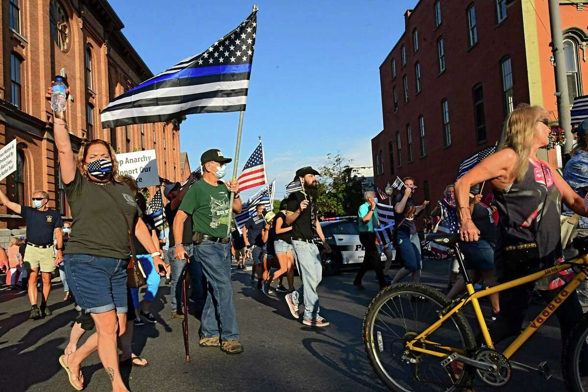 People march down Broadway during a rally in support of the police on Thursday, July 30, 2020 in Saratoga Springs, N.Y. A large counter protest was also present. (Lori Van Buren/Times Union)