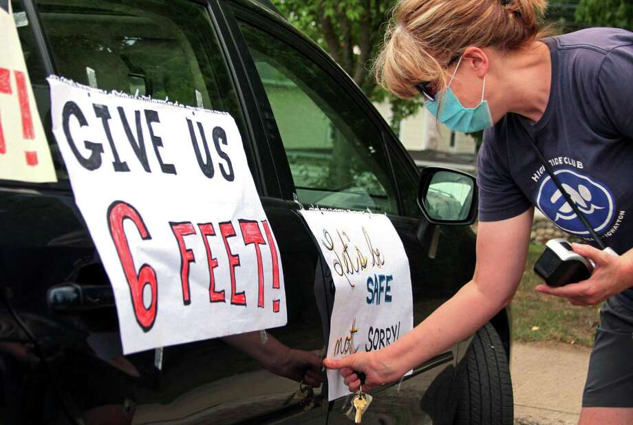 "Janet Jacobs, a teacher at Wolfpit Elementary School, puts posters on her vehicle before the start of a ""School Safety First"" teacher caravan at Brien McMahon High School in Norwalk, Conn., on Thursday July 29, 2020. This was one of many held all across the state today. The purpose of the coordinated day of action is to amplify demands for safety and health precautions and full, equitable funding when school buildings reopen this fall.