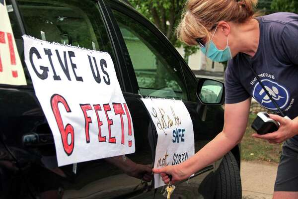 """Janet Jacobs, a teacher at Wolfpit Elementary School, puts posters on her vehicle before the start of a """"School Safety First"""" teacher caravan at Brien McMahon High School in Norwalk, Conn., on Thursday July 29, 2020. This was one of many held all across the state today. The purpose of the coordinated day of action is to amplify demands for safety and health precautions and full, equitable funding when school buildings reopen this fall."""
