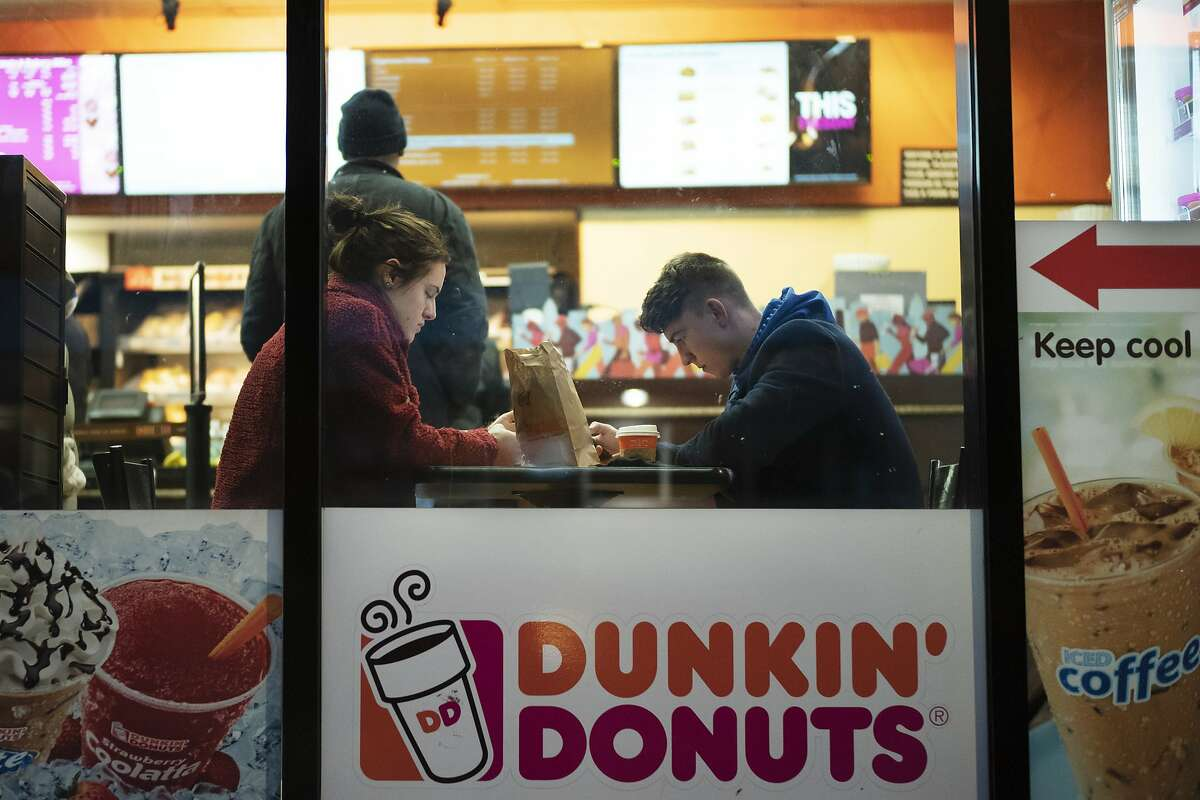 FILE- In this Jan. 30, 2019, file photo customers sit inside a Dunkin' Donuts in New York.