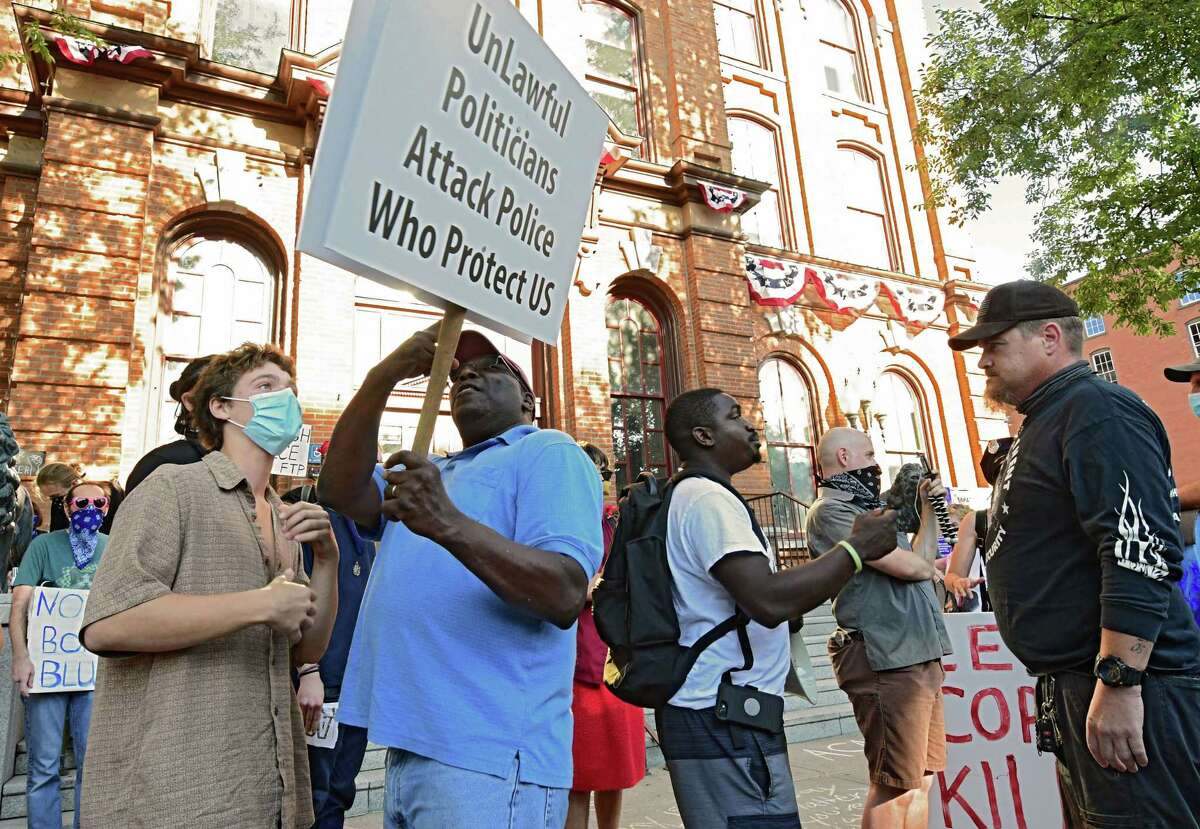 People rallying for police, second from left, and man at right, engage in conversation with Black Lives Matter counter protesters, left, and second from right, in front of City Hall on Thursday, July 30, 2020 in Saratoga Springs, N.Y. (Lori Van Buren/Times Union)
