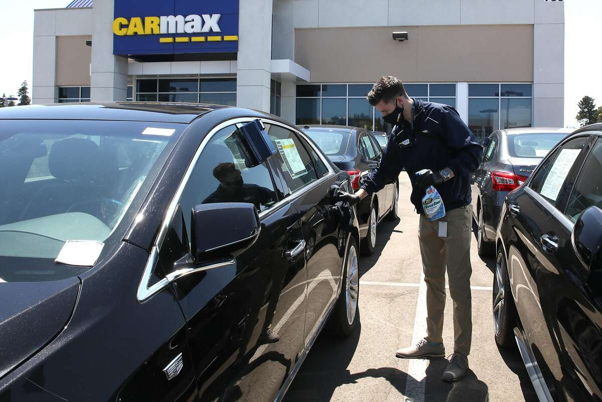 Sales Consultant Jordan Kanady disinfects a Cadillac that a customer will test drive at the San Jose Carmax, on Thursday, July 30, 2020, in San Jose, Calif.
