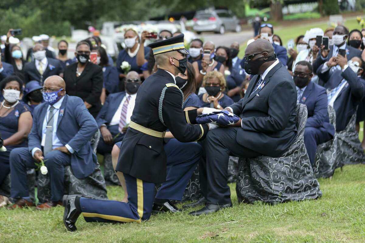 ATLANTA, GEORGIA - JULY 30: A member of the Honor Guard presents the American flag that was on the casket of the late Rep. John Lewis (D-GA) to his son, John-Miles Lewis during Rep. Lewis's burial at South-View Cemetery on July 30, 2020 in Atlanta, Georgia. Lewis, a civil rights icon and fierce advocate of voting rights for African Americans, died on July 17 at the age of 80. (Photo by Alyssa Pointer-Pool/Getty Images)