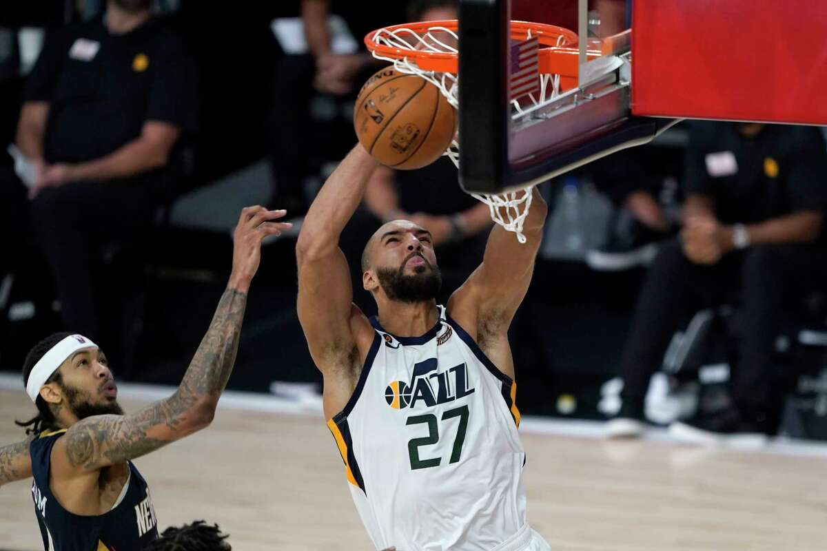 LAKE BUENA VISTA, FLORIDA - JULY 30: Utah Jazz's Rudy Gobert #27 heads to the basket past New Orleans Pelicans' Brandon Ingram, left, during the second half of an NBA basketball game on July 30, 2020 in Lake Buena Vista, Florida. NOTE TO USER: User expressly acknowledges and agrees that, by downloading and or using this photograph, User is consenting to the terms and conditions of the Getty Images License Agreement. (Photo by Ashley Landis-Pool/Getty Images)
