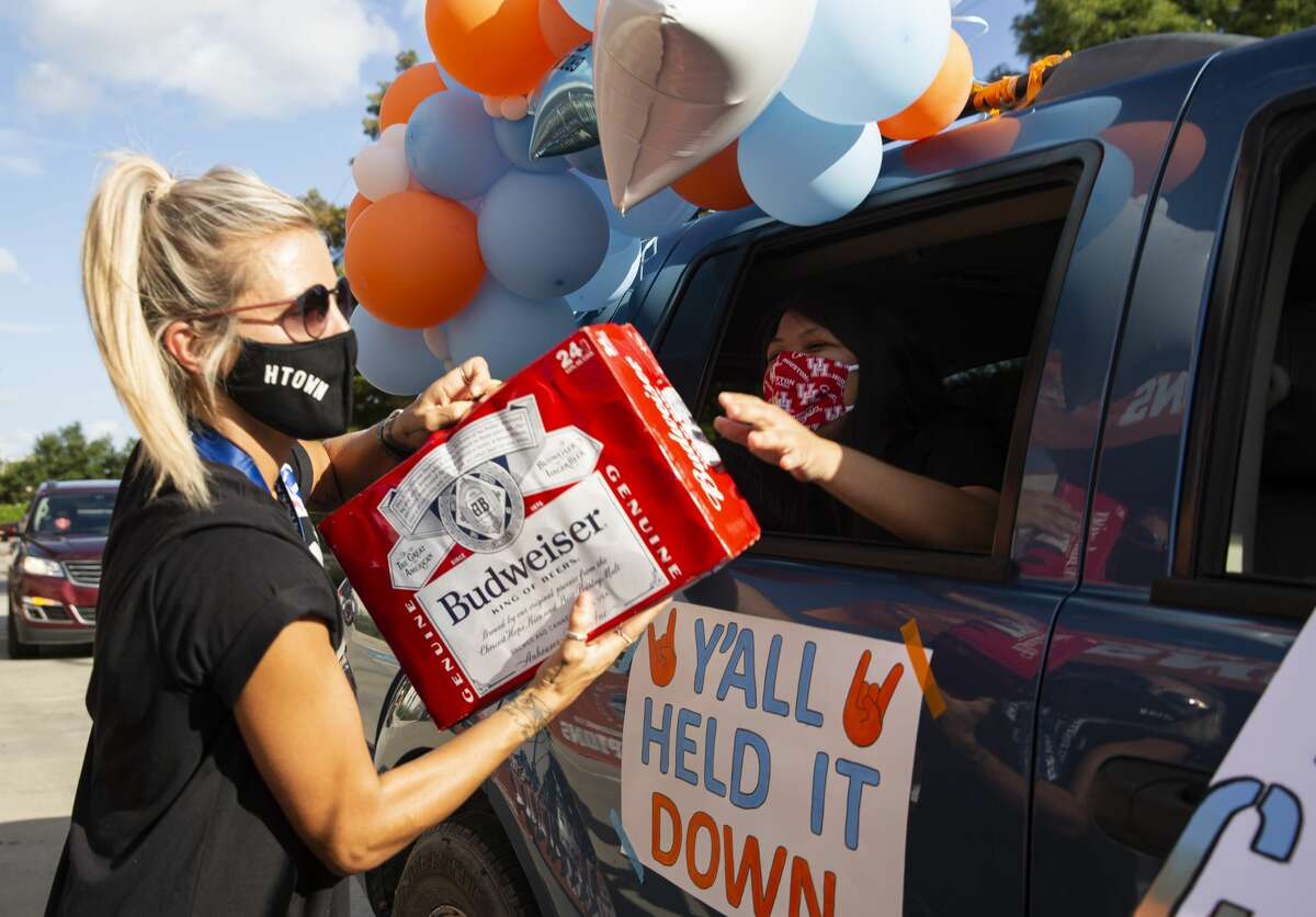 Houston Dash Rachel Daly receives a pack of beer while celebrating NWSL Challenge Cup Championship at a drive-thru setting with fans Thursday, July 30, 2020, outside BBVA Stadium in Houston. Daly was honored the NWSL Challenge Cup Most Valuable Player and NWSL Challenge Cup Golden Boot.