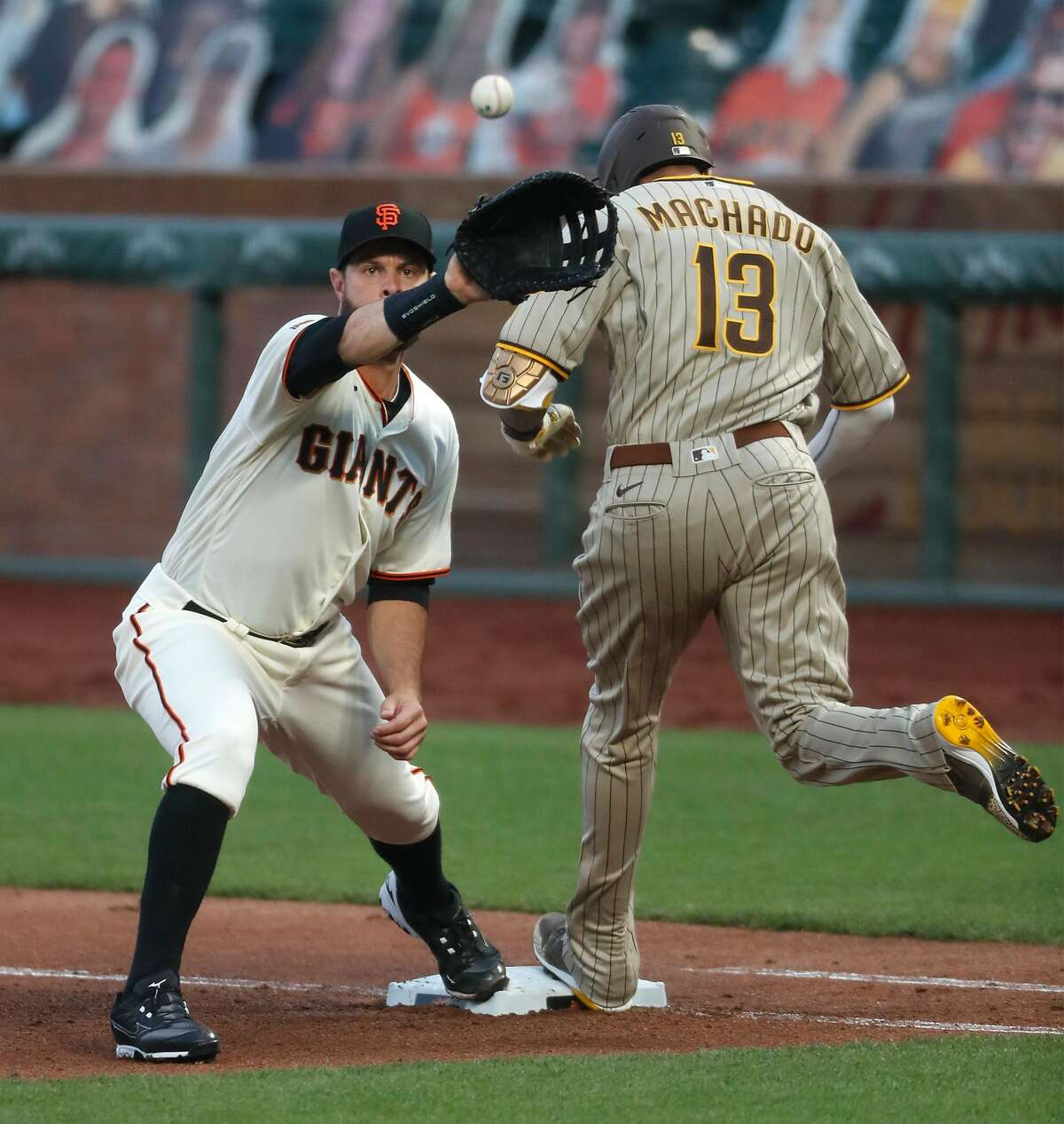 San Diego Padres' Manny Machado beats out an infield hit as San Francisco Giants' Brandon Belt awaits the throw in 4th inning during MLB game at Oracle Park in San Francisco, Calif., on Thursday, July 30, 2020.
