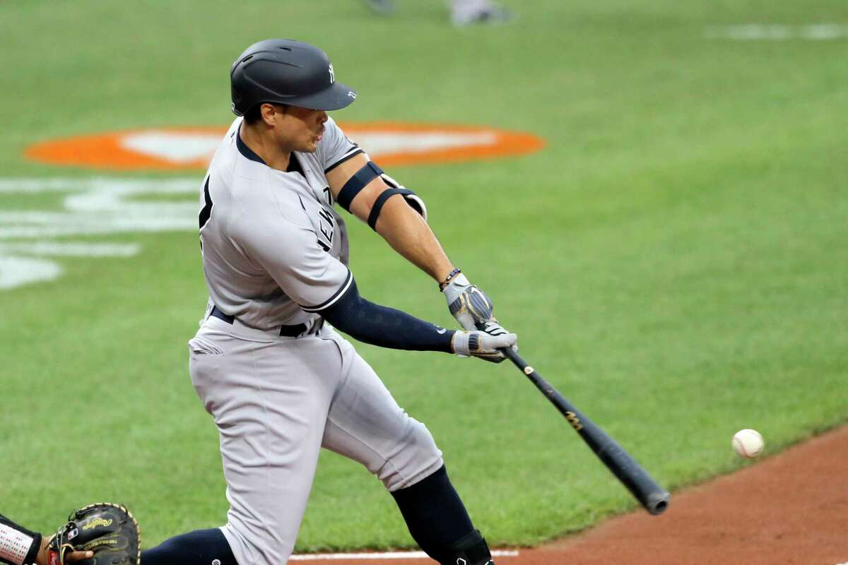 New York Yankees' Giancarlo Stanton swings at a pitch from Baltimore Orioles starting pitcher John Means during the first inning of a baseball game, Thursday, July 30, 2020, in Baltimore. Yankees' Aaron Judge scored on the play. (AP Photo/Julio Cortez)