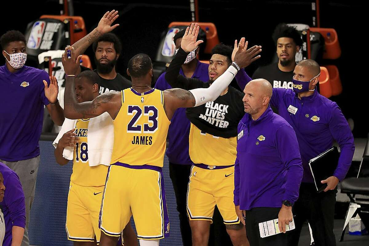 Los Angeles Lakers' LeBron James (23) celebrates with his teammates after they defeated the Los Angeles Clippers in an NBA basketball game Thursday, July 30, 2020, in Lake Buena Vista, Fla. (Mike Ehrmann/Pool Photo via AP)