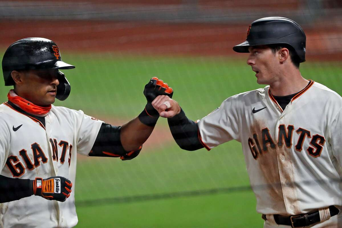 San Francisco Giants' Mike Yastrzemski fist bumps Donovan Solano after Yastrzemski scored on Solano's sacrifice fly to tie game at 6-6 in the 8th inning against San Diego Padres during MLB game at Oracle Park in San Francisco, Calif., on Thursday, July 30, 2020.