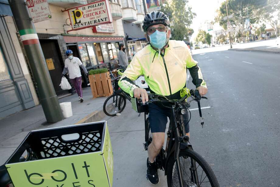 Volunteer Kieran Buckley gets on an e-bike to deliver an order from Il Pollaio restaurant. A group of volunteers known as 'North Beach Delivers' offer free delivery services for local restaurants impacted by the COVID-19 coronavirus, connecting them with customers in the North Beach neighborhood of San Francisco on July 30, 2020. Photo: Douglas Zimmerman/SFGATE / SFGATE