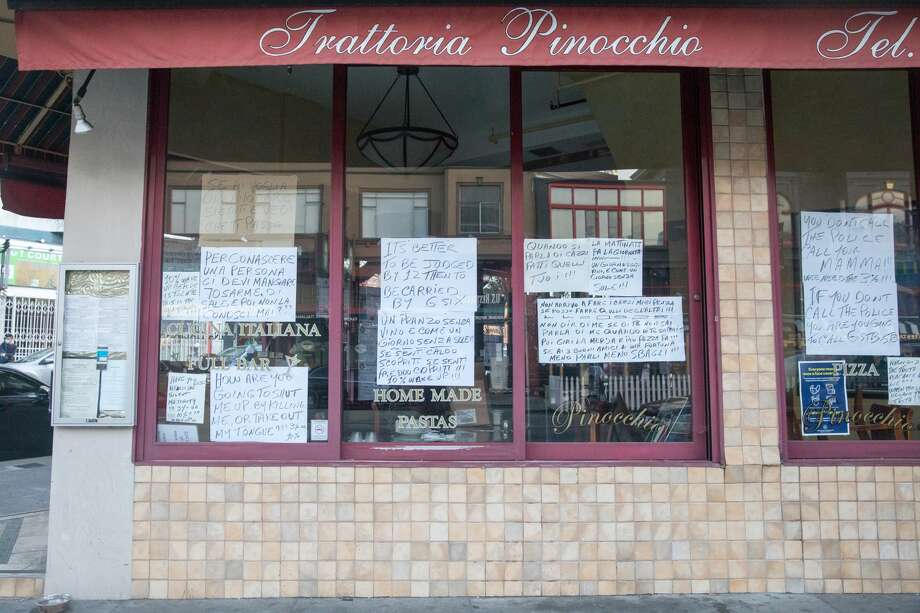 The windows of Trattoria Pinocchio restaurant in the North Beach neighborhood of San Francisco, California on July 30, 2020. They are covered with homemade written signs that are creating a stir. Photo: Douglas Zimmerman/SFGATE / SFGATE
