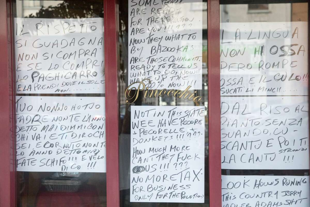 The windows of Trattoria Pinocchio restaurant in the North Beach neighborhood of San Francisco, California on July 30, 2020. They are covered with homemade written signs that are creating a stir.