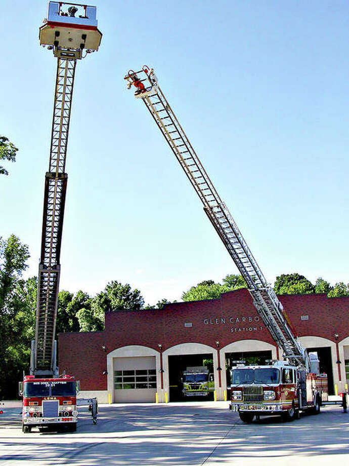 Glen Carbon Fire District officials show off their latest vehicle acquisitions. At left is a 105-foot 1990 ladder truck acquired from the Lena Illinois Fire District. At right is a 75-foot 2008 ladder truck acquired from the Lake Ozark Fire District in Missouri.