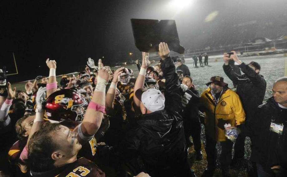 St. Joseph coach Joe Della Vecchia holds aloft the Class L championship trophy. Photo: GameTimeCT / File Photo